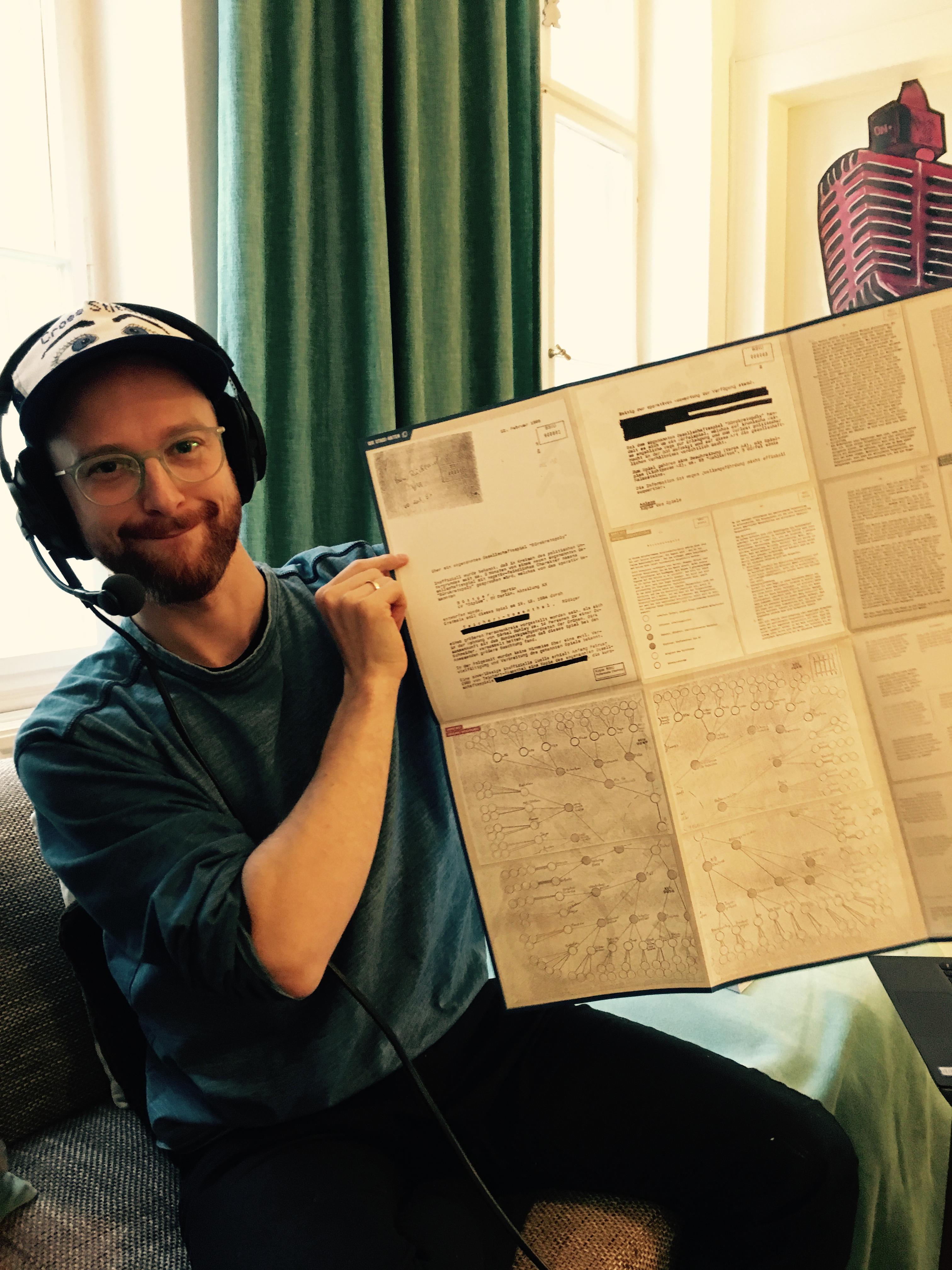 """Geis präsentiert die Stasi-Akte von """"Bürokratpoly"""", die auf der Rückseite des Spiels abgebildet ist"""