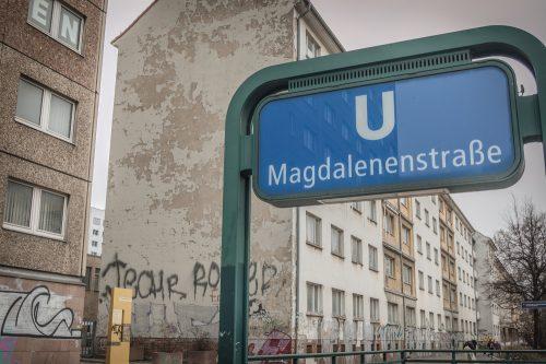 """U-Bahn-Schild an der Haltestelle """"Magdalenenstraße"""" in Berlin-Lichtenberg, im Hintergrund ist der Zugang zum Gelände Stasi-Archivs zu sehen"""